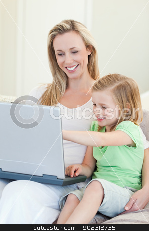 Mother and daughter with laptop on couch stock photo, Mother and daughter together with laptop on couch by Wavebreak Media