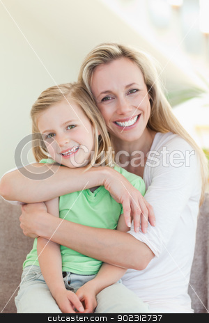 Mother hugging her daughter on couch stock photo, Mother hugging her daughter on the couch by Wavebreak Media