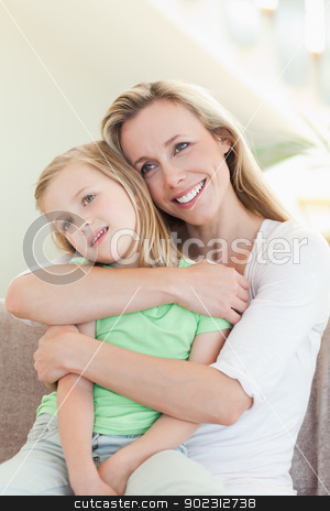 Mother embracing daughter on sofa stock photo, Mother embracing daughter on the sofa by Wavebreak Media
