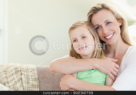 Mother embracing daughter on couch stock photo, Mother embracing daughter on the couch by Wavebreak Media