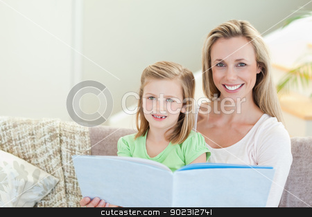 Mother and daughter reading a magazine on the sofa stock photo, Mother and daughter reading a magazine together on the sofa by Wavebreak Media