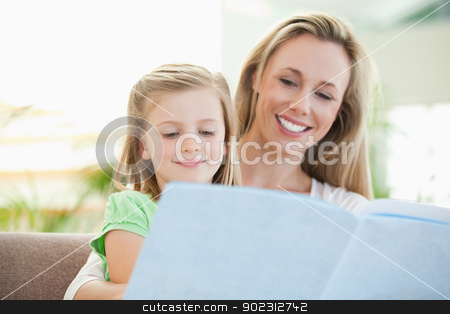 Mother and daughter reading a magazine on the couch stock photo, Mother and daughter reading a magazine together on the couch by Wavebreak Media