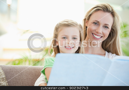 Mother and daughter reading on the sofa stock photo, Mother and daughter reading together on the sofa by Wavebreak Media