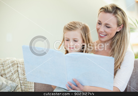 Mother and daughter reading on the couch stock photo, Mother and daughter reading together on the couch by Wavebreak Media