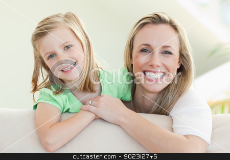 Smiling mother and daughter on the sofa stock photo, Smiling mother and daughter together on the sofa by Wavebreak Media