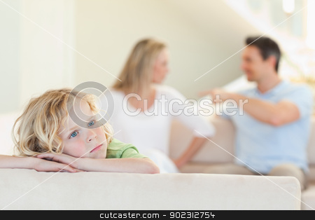 Sad boy with fighting parents behind him stock photo, Sad boy with his fighting parents behind him by Wavebreak Media