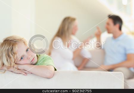 Sad boy with arguing parents behind him stock photo, Sad boy with his arguing parents behind him by Wavebreak Media