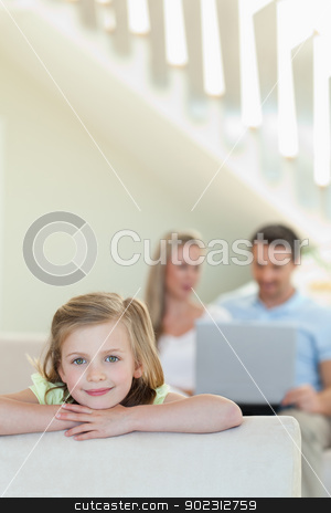 Smiling little girl with parents behind her stock photo, Smiling little girl with her parents behind her by Wavebreak Media