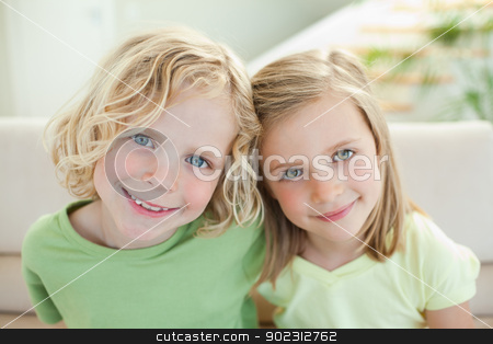 Smiling siblings on the sofa stock photo, Smiling siblings together on the sofa by Wavebreak Media