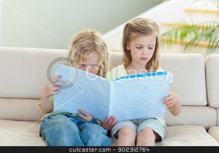 Siblings reading magazine on the sofa stock photo, Siblings reading magazine together on the sofa by Wavebreak Media