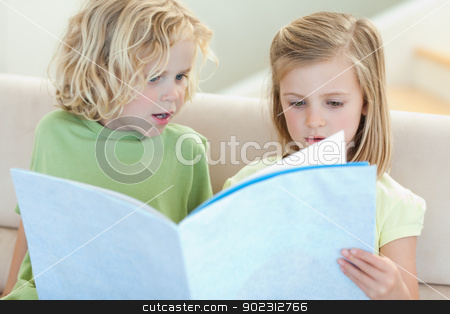 Siblings on the sofa reading magazine stock photo, Siblings on the sofa reading magazine together by Wavebreak Media
