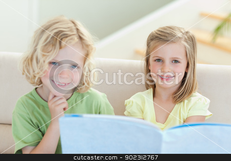 Siblings on the couch reading magazine stock photo, Siblings on the couch reading magazine together by Wavebreak Media