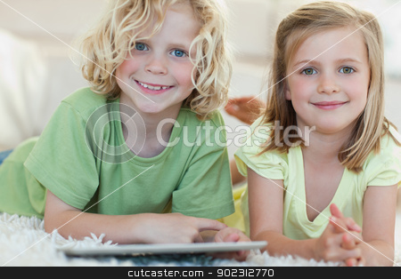 Siblings using tablet on the floor stock photo, Siblings using tablet together on the floor by Wavebreak Media