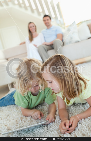 Siblings using tablet on the carpet with parents behind them stock photo, Siblings using tablet together on the carpet with parents behind them by Wavebreak Media