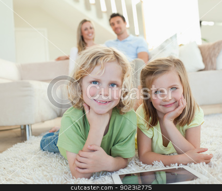 Children on the carpet with tablet and parents behind them stock photo, Children on the carpet together with tablet and parents behind them by Wavebreak Media