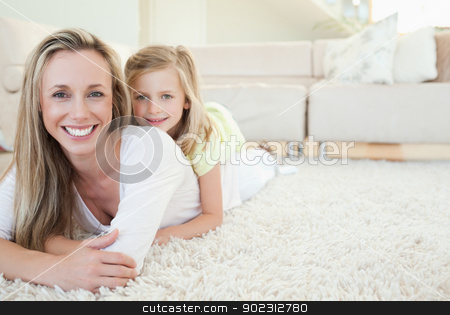 Mother and daughter lying on the floor stock photo, Mother and daughter lying on the floor together by Wavebreak Media