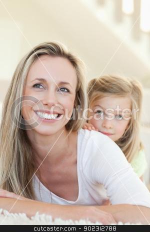 Smiling mother and daughter on the floor stock photo, Smiling mother and daughter together on the floor by Wavebreak Media