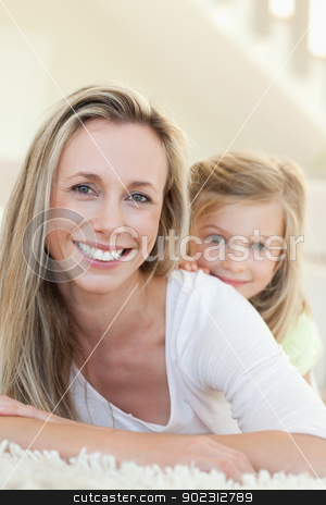 Smiling mother and daughter on the carpet stock photo, Smiling mother and daughter together on the carpet by Wavebreak Media