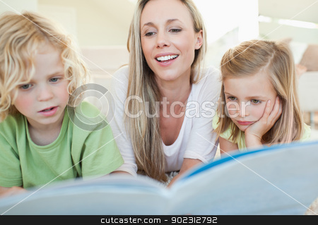 Mother reading magazine with her children stock photo, Mother reading magazine together with her children by Wavebreak Media