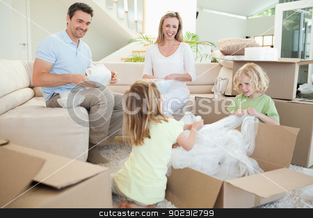 Family unpacking cardboard box in the living room stock photo, Family unpacking cardboard box in the living room together by Wavebreak Media