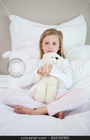 Girl hugging her teddy on the bed stock photo, Little girl hugging her teddy on the bed by Wavebreak Media