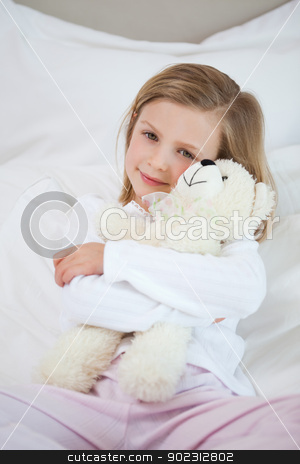 Girl embracing her teddy on the bed stock photo, Little girl embracing her teddy on the bed by Wavebreak Media