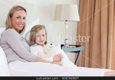 Side view of mother and daughter sitting on the bed stock photo, Side view of mother and daughter sitting together on the bed by Wavebreak Media