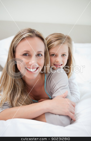 Girl laying on her mothers back stock photo, Little girl laying on her mothers back by Wavebreak Media