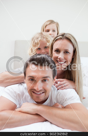 Playful family on the bed stock photo, Playful family together on the bed by Wavebreak Media