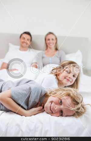 Family taking a rest on the bed stock photo, Family taking a rest together on the bed by Wavebreak Media