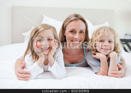 Mother embracing her children stock photo, Mother embracing her children on the bed by Wavebreak Media