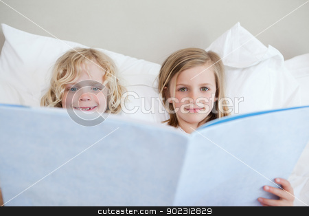Brother and sister reading bedtime story stock photo, Brother and sister reading bedtime story together by Wavebreak Media