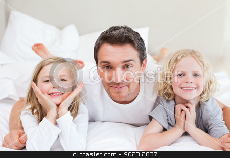 Father lying on the bed with his children stock photo, Father lying on the bed together with his children by Wavebreak Media