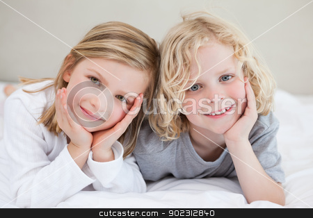 Brother and sister lying on the bed stock photo, Brother and sister lying on the bed together by Wavebreak Media