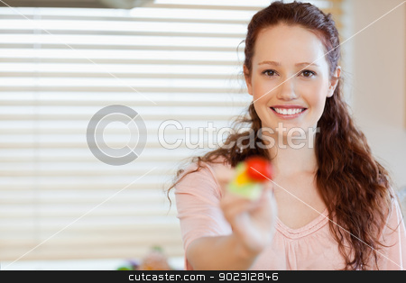 Girl offering a mouthful of salad stock photo, Smiling girl offering a mouthful of salad by Wavebreak Media