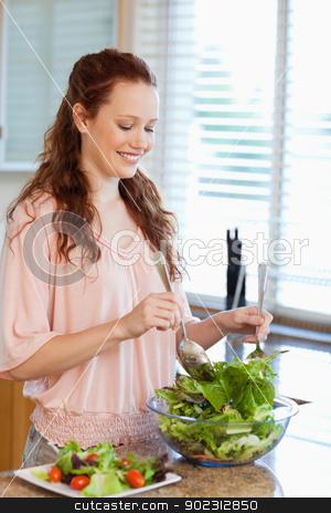 Woman stirring bowl of salad stock photo, Woman stirring bowl of green salad by Wavebreak Media