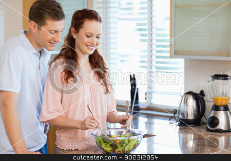 Couple with bowl of salad in the kitchen stock photo, Couple with bowl of healthy salad in the kitchen by Wavebreak Media