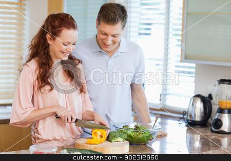 Man watching his girlfriend preparing a salad stock photo, Man watching his girlfriend preparing a salad in the kitchen by Wavebreak Media