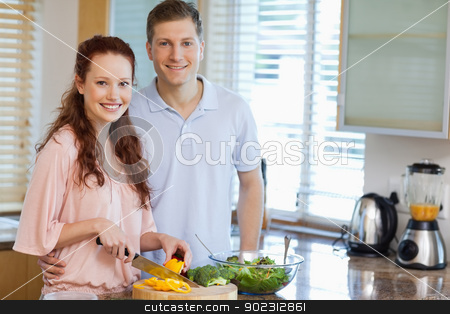 Couple in the kitchen preparing salad stock photo, Smiling couple in the kitchen preparing salad by Wavebreak Media