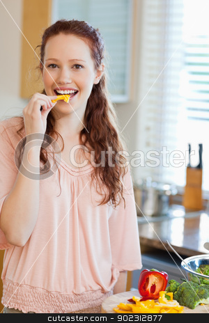Woman eating bell pepper stock photo, Woman eating yellow bell pepper by Wavebreak Media