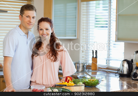 Couple standing behind kitchen counter stock photo, Couple standing behind kitchen counter together by Wavebreak Media