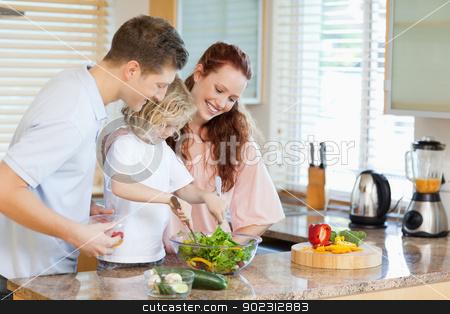 Couple letting their child stir the salad stock photo, Couple letting their young child stir the salad by Wavebreak Media
