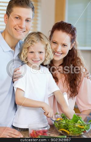 Happy family preparing salad together stock photo, Happy smiling family preparing salad together by Wavebreak Media
