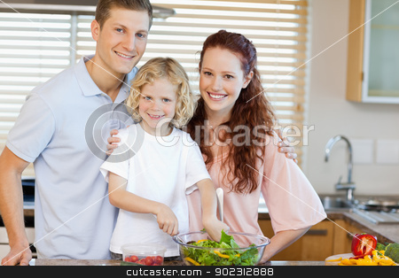 Smiling family preparing salad together stock photo, Happy smiling family preparing salad together by Wavebreak Media