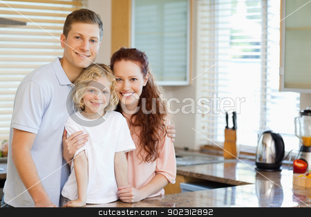 Smiling family standing behind the kitchen counter stock photo, Smiling family standing behind the kitchen counter together by Wavebreak Media