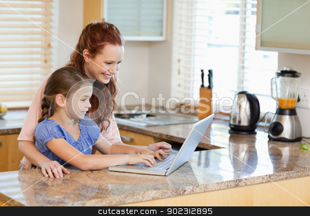 Mother and daughter with laptop in the kitchen stock photo, Mother and daughter together with laptop in the kitchen by Wavebreak Media