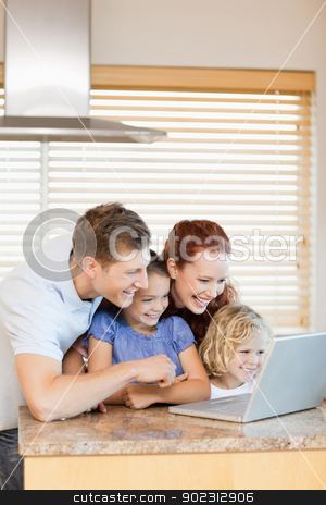 Family exploring the internet in the kitchen stock photo, Family exploring the internet in the kitchen together by Wavebreak Media