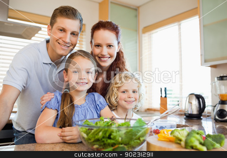 Family standing behind the kitchen counter stock photo, Family standing together behind the kitchen counter by Wavebreak Media