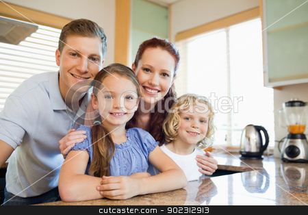 Family standing together behind the kitchen counter stock photo, Smiling family standing together behind the kitchen counter by Wavebreak Media