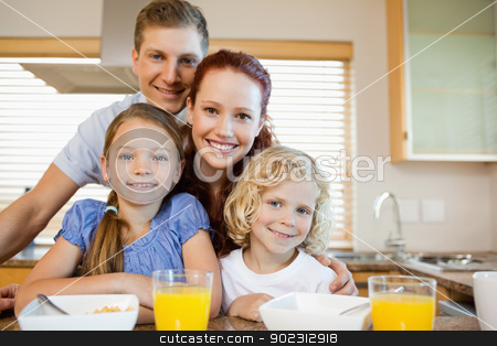 Family with breakfast behind the kitchen counter stock photo, Family together with breakfast behind the kitchen counter by Wavebreak Media